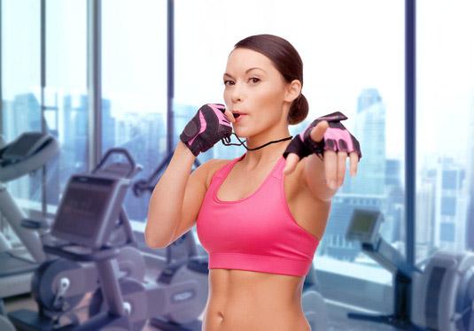 femme coach tenant un sifflet dans une salle de fitness