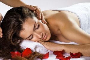 Jolie femme alongée se faisant masser délicatement