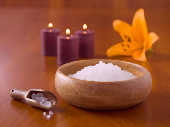 Du sel, une orchidéeet de belles bougies sur une table en bois