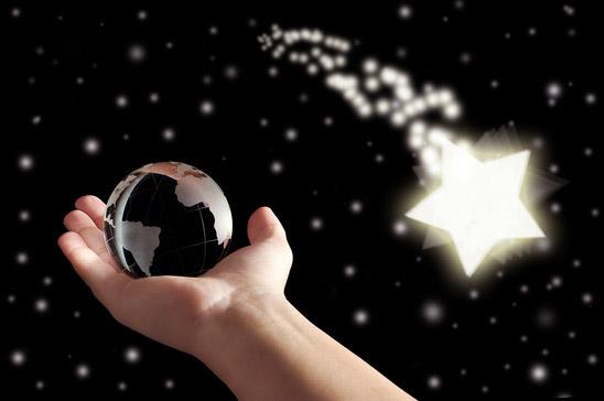Une main portant une petite boule de cristal en direction des étoiles